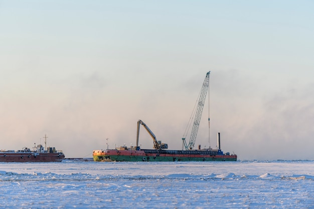 Barge with crane. dredger working at sea. sunset in arctic sea. construction marine offshore works. dam building, crane, barge, dredger.