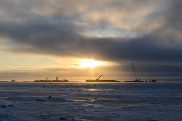 Barge with crane. dredger working at sea. sunset in arctic sea. construction marine offshore works.