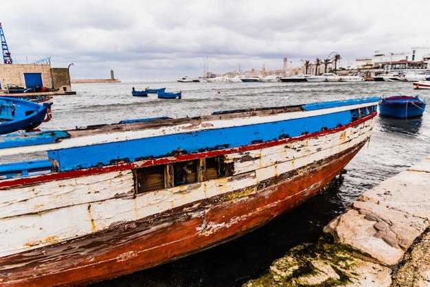 Bari, italy - march 12, 2019: blue wooden boat washed by time and waves in a harbor.