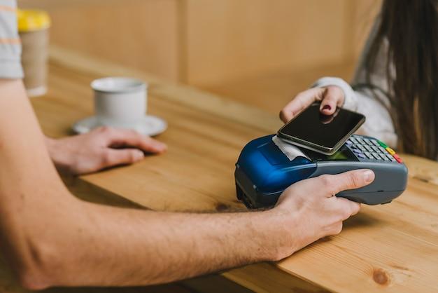 Barista che accetta pagamento con smartphone