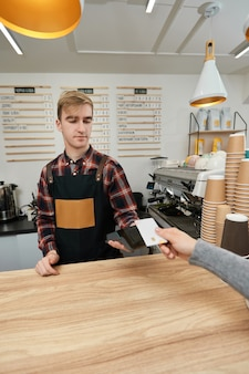 Barista accepts payment from credit card via pos machine in coffee shop customer hand holding credit card near nfc terminal.