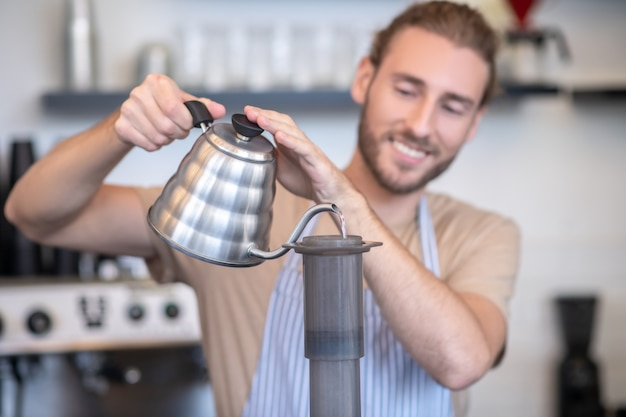 バリスタ、エアロプレス。コーヒーを作るためにエアプレスに水を注ぐ鉄のティーポットとエプロンでうれしそうなひげを生やした若い男性バリスタ