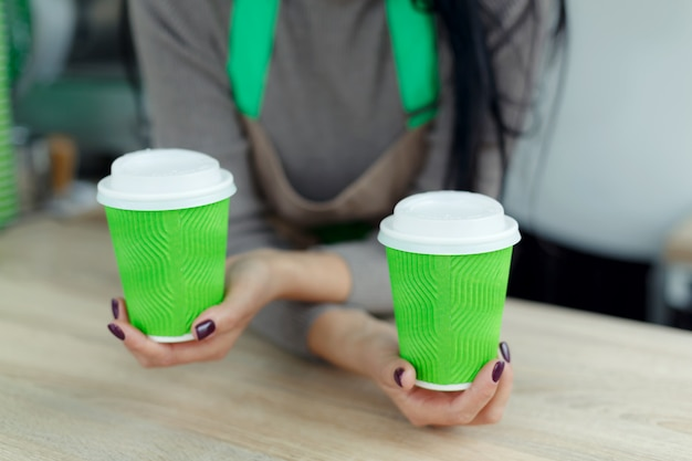 Barista in apron is holding in hands hot coffee in green takeaway paper cup.