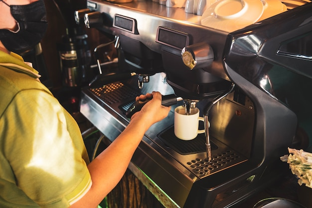 Бариста, азиатская женщина заваривание кофе с помощью кофеварки.