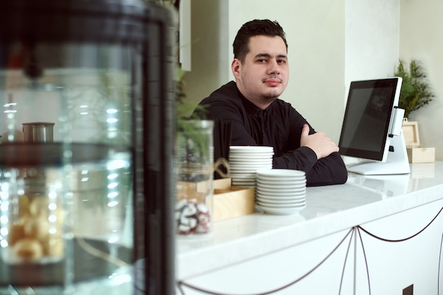 Barista at the bar behind the monitor. in front of him is a showcake with cupcakes and sweeties