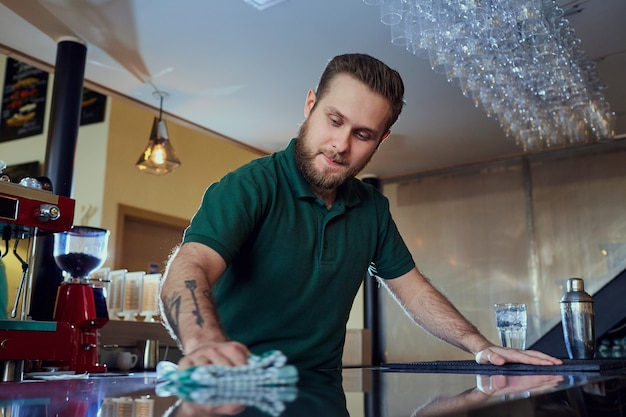 바리 스타 바텐더가 바의 표면을 닦습니다. 카페 레스토랑에서 청소.