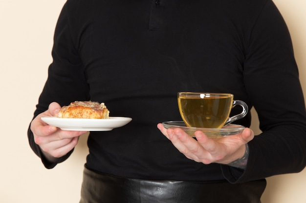 Barista in black suit holding cake and hot cup of green tea