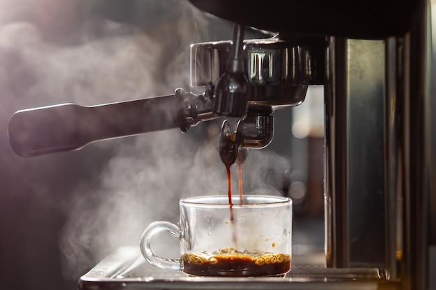 작은 커피 숍에서 고압 에스프레소 머신을 사용하여 에스프레소 커피를 추출하는 바리 스타.