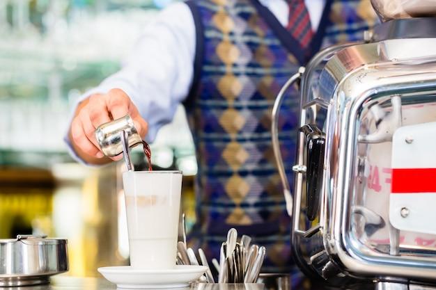 Barista in cafe pouring espresso shot in latte macchiato