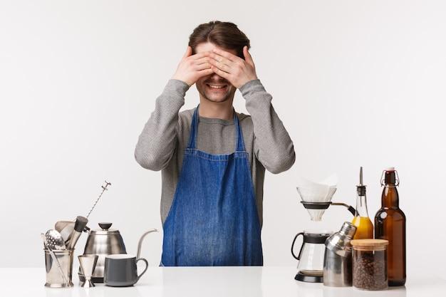 バリスタ、カフェワーカー、バーテンダーのコンセプト。面白いとかわいい若い男性従業員が休憩中に楽しんで、ティーポットとバーのカウンターの近くにエプロンを立って、コーヒーを作って、目を閉じて、笑顔