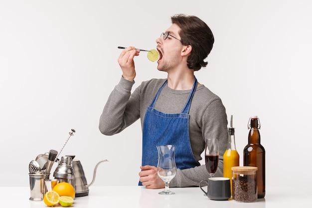 バリスタ、カフェワーカー、バーテンダーのコンセプト。エプロンでお酒を飲んで、カクテルを準備しながらライムのスライスを食べて面白い屈託のない若い男