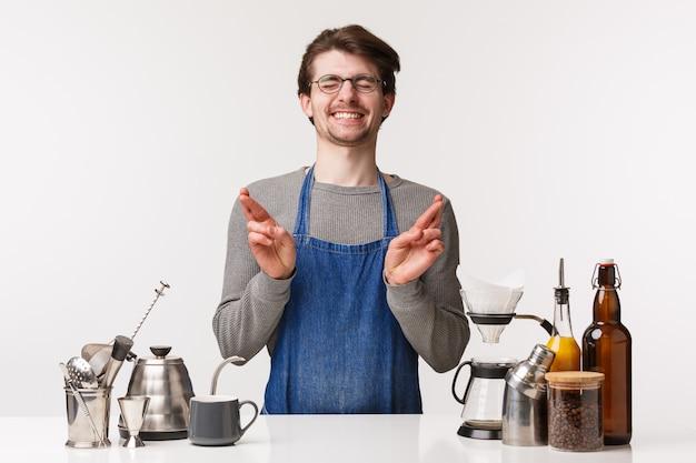 バリスタ、カフェワーカー、バーテンダーのコンセプト。エプロンで希望に満ちたかわいい興奮している従業員、富を祈る中小企業の所有者、運指を組んで、バーカウンターでコーヒーを作りながら願い事をする