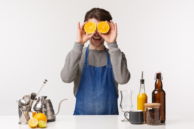 バリスタ、カフェワーカー、バーテンダーのコンセプト。ドリンクを作る青いエプロンで陽気な幸せな男性従業員の肖像画は、アイマスクとカメラの笑顔のようなオレンジの2つのスライスを保持し、バーのカウンターの近くに立つ