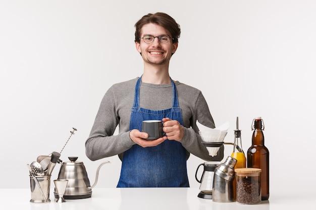 バリスタ、カフェワーカー、バーテンダーのコンセプト。エプロンの陽気な快適な若い男性従業員の肖像画は、誰もがおいしい飲み物、コーヒーを作って、お茶を持って、カメラを笑顔に誘う