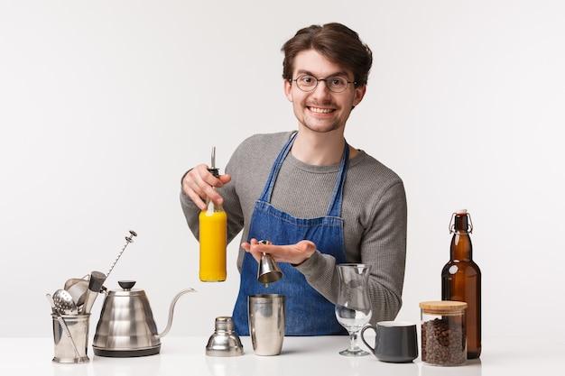 バリスタ、カフェワーカー、バーテンダーのコンセプト。カメラを笑顔でコーヒーや特別な飲み物を作りながらシェーカーにジュースを注いでそれを注ぐエプロンでフレンドリーで陽気な楽しい男の肖像