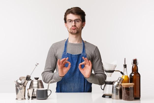 バリスタ、カフェワーカー、バーテンダーのコンセプト。感銘を受けた、喜ばしい白人男性の肖像画、エプロンとメガネの従業員は悪い兆候ではなく、確認で大丈夫を示し、良いコーヒー製造方法を承認