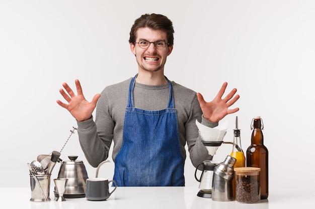 バリスタ、カフェワーカー、バーテンダーのコンセプト。失礼な顧客に攻撃的でイライラしたコーヒーを感じさせるエプロンで腹を立てた腹が立つ若い男性の肖像画、