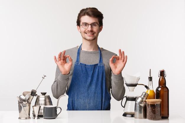 バリスタ、カフェワーカー、バーテンダーのコンセプト。エプロン笑顔で満足し、満足している若い男性従業員の肖像画は、あなたがコーヒーを好きになることを保証し、カプチーノに大丈夫のサインを見せます