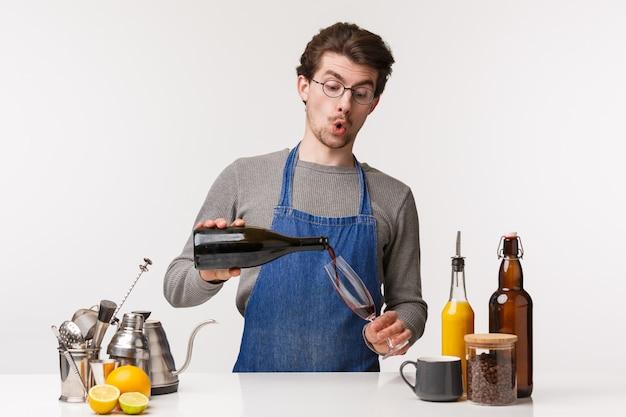 バリスタ、カフェワーカー、バーテンダーのコンセプト。グラスにワインを注ぐと面白がって笑っているエプロンで愚かなハンサムな若い男の肖像は、夕食の準備中にアルコールを一口必要、