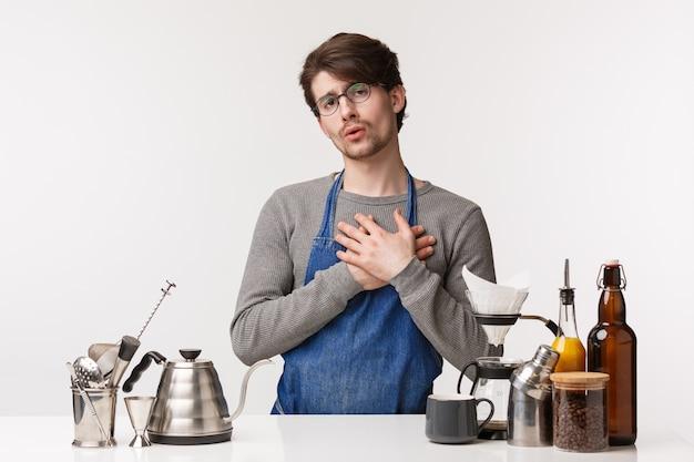 バリスタ、カフェワーカー、バーテンダーのコンセプト。コーヒーを作るエプロンで触れたハンサムな若い男性従業員の肖像画、心に触れ、お世辞を感じる、顧客は彼のカプチーノが好き