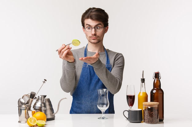 バリスタ、カフェワーカー、バーテンダーのコンセプト。ライムのスライスを保持しているエプロンの若い白人男性の肖像画、カクテルを準備、グラスでドリンクを作る、フルーツに焦点を当てて見て