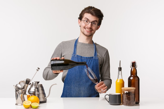 Barista, cafe worker and bartender concept. handsome friendly smiling guy in apron standing at bar counter, hold bottle and pouring glass of wine to customer, looking at customer