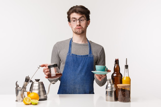 Barista, cafe worker and bartender concept. portrait of indecisive careless young bored male employee grimacing look away uncertain, hold kettle with filter coffee and cup,