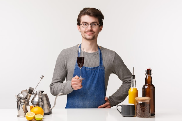 Barista, cafe worker and bartender concept. portrait of pleased happy successful male entrepreneur of small business delighted after closing store pouring glass of wine and smile satisfied