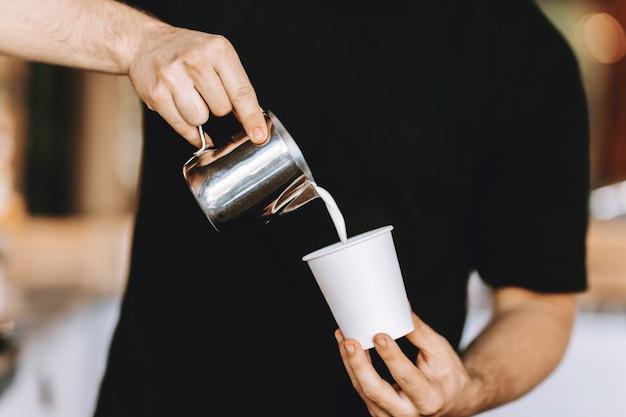 Бариста аккуратно наливает молоко в стакан в современной кофейне. .
