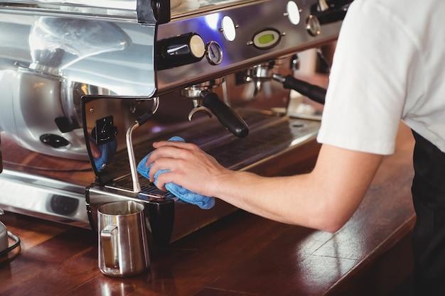 Barista cleaning coffee machine
