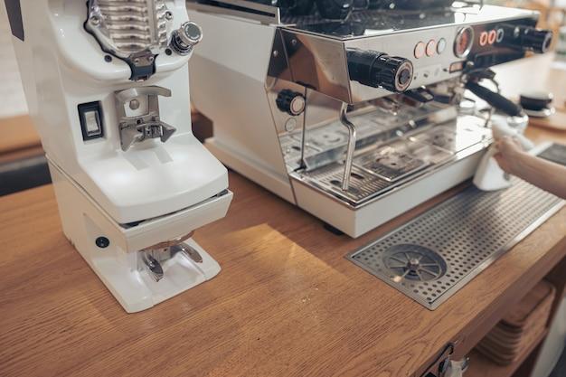 カフェテリアでプロのコーヒーマシンを掃除するバリスタ