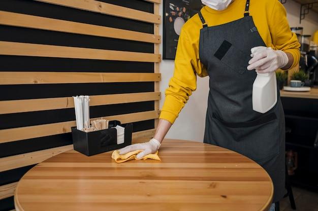 의료 마스크를 착용하는 동안 바리 스타 청소 테이블