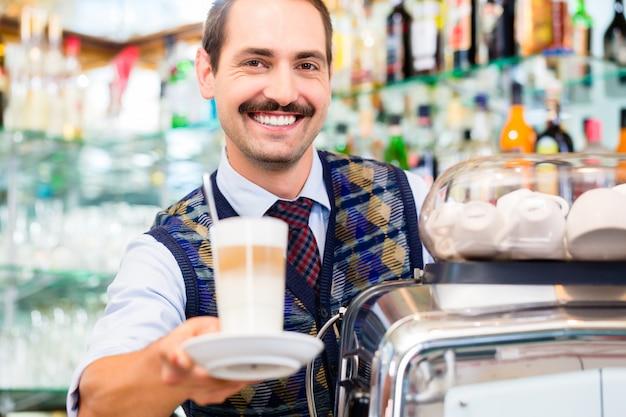 Barista in coffee bar offers latte macchiato in glass