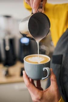 Бариста украшает чашку кофе молоком