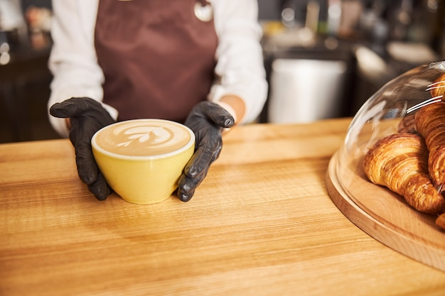 Barista demonstrating fresh hot coffee in the cafe
