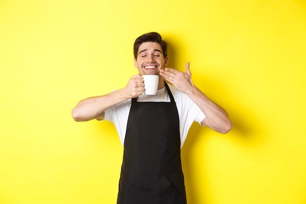 Бариста наслаждается запахом кофе в кружке, довольный, с закрытыми глазами, в черном фартуке.