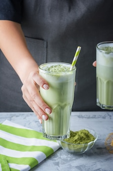 Barista girl holds out a glass with a healthy drink. latte made from matcha green tea