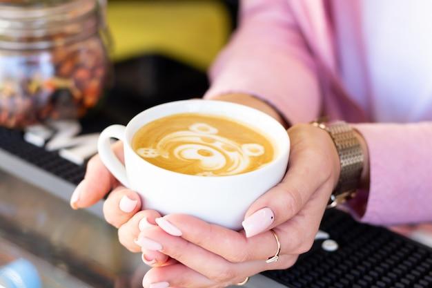 Девушка-бариста подает готовый латте-кофе с рисунком прекрасного мишки. крупный план