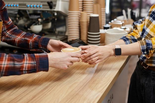 바리스타가 고객에게 신선한 커피 카푸치노 한 잔을 제공합니다.
