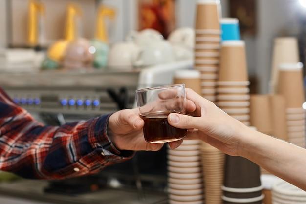 바리스타가 고객에게 신선한 커피 한 잔을 제공합니다.