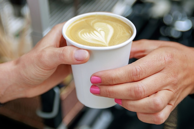 Barista giving to the customer paper cup with cappuccino coffee