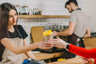 Barista giving drink to customer