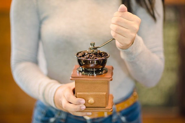 Barista grinding coffee by hand on a vintage coffee grinder