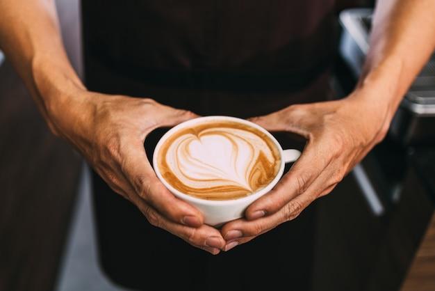 Бариста в руках держит чашку горячего латте в форме сердца.