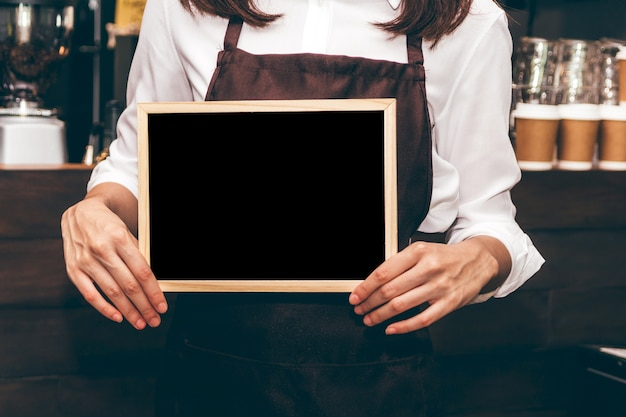 Barista holding chalkboard  in coffee shop restaurant