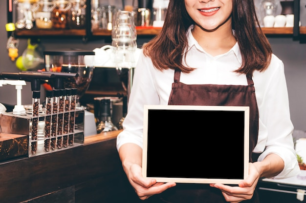 Barista holding chalkboard  in coffee shop restaurant