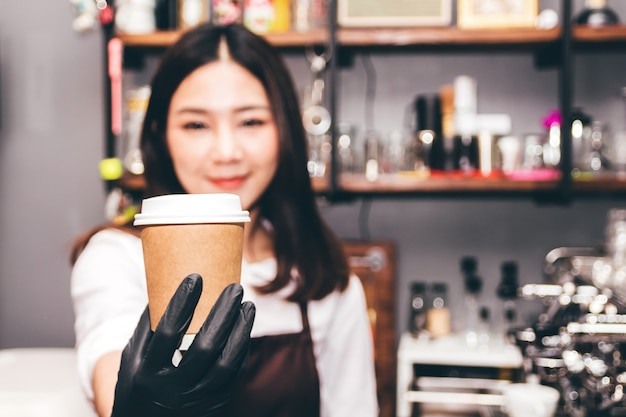Barista holding coffee in coffee shop