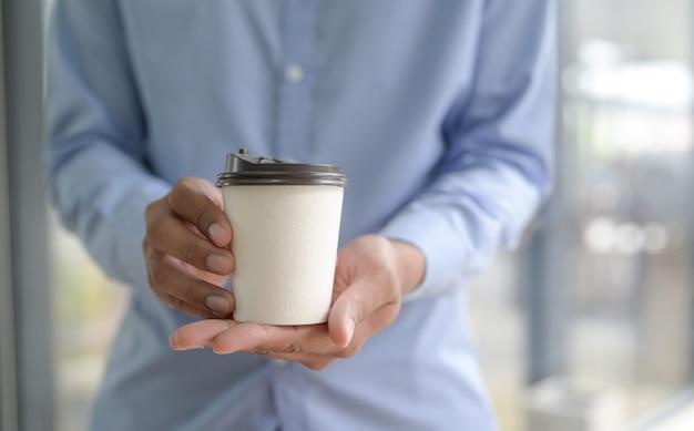 Бариста держит чашку кофе на вынос