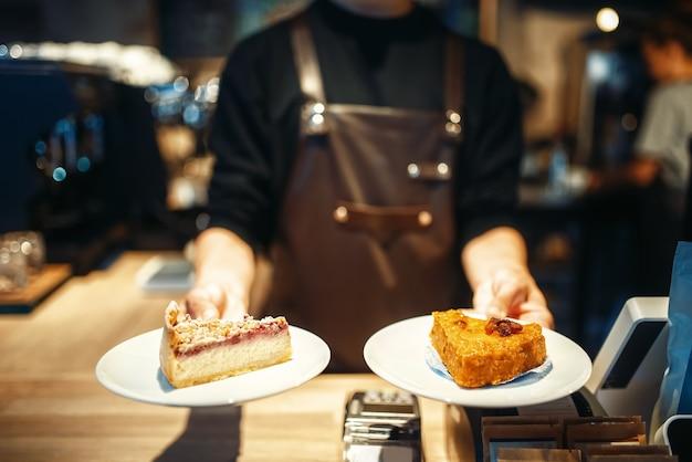 Бариста держит в руках тарелки со сладким десертом