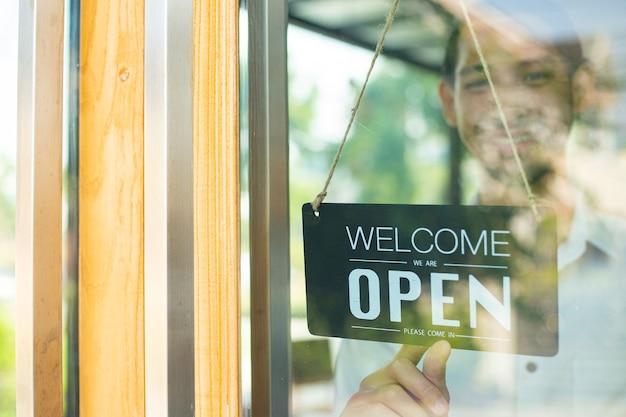 歓迎の顧客のためのオープンブラックカラーの木製看板を保持しているバリスタは、コーヒーショップでサービスに来ます